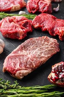 Płaski stek wołowy z kawałkami żelaza, z ziołami, przyprawami na czarnym stole