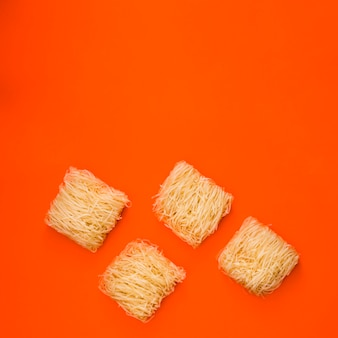 Płaski surowy makaron nad wibrującym pomarańczowym tłem