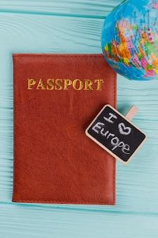 Płaski świecki brązowy skórzany paszport z małą tablicą i kulą ziemską na niebieskim tle. podróżuj po koncepcji europy.