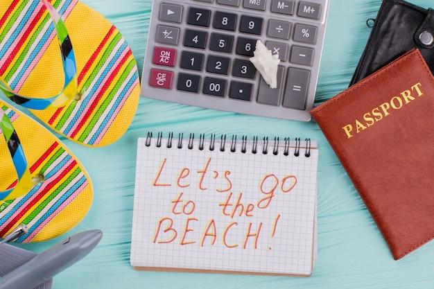 Płaski świecki projekt koncepcji podróży z paszportem, sandałami i kalkulatorem na niebieskim tle. chodźmy na plażę zapisaną w notatniku.