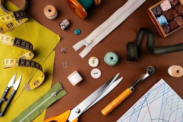 Płaski świecki skład akcesoriów do szycia, nożyczki, wzory, tkaniny na brązowym tle, widok z góry. pulpit projektanta mody, krawca w atelier. koncepcja szycia w stylu vintage.