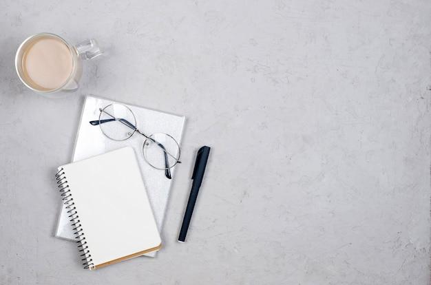 Płaski świeckich, biurowy widok z góry. szare biurko z pustym półfabrykatem, zapasami, szklankami i filiżankami kawy. minimalne biuro w domu lub nowoczesna przestrzeń robocza dla freelancerów.