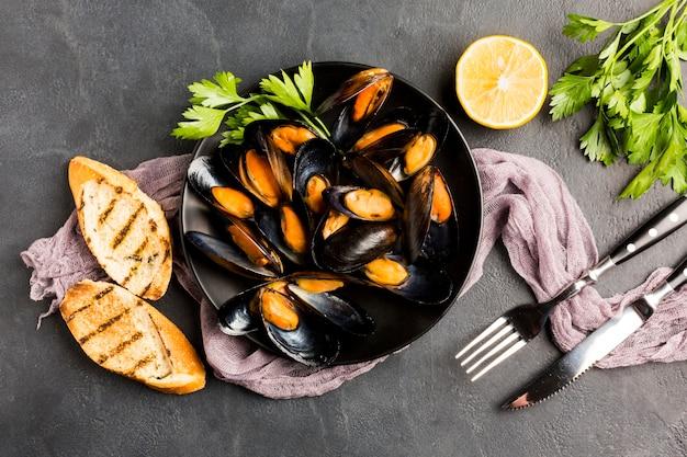 Płaski talerz gotowanych małży i sztućców