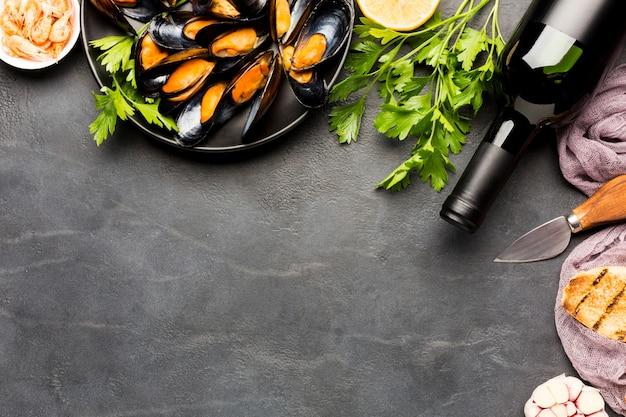 Płaski talerz gotowanych małży i wina z copyspace