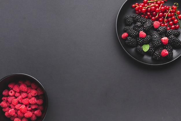 Płaski talerz i miska świeżych jagód