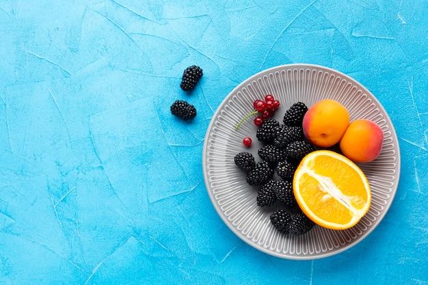 Płaski talerz owoców i jagód z copyspace