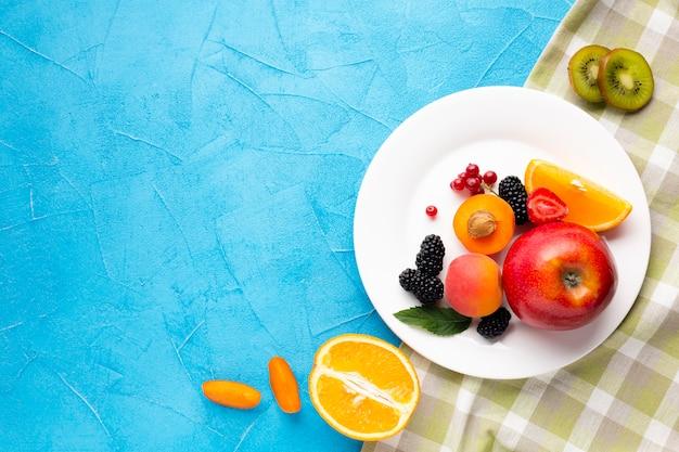 Płaski talerz świeżych jagód i owoców z copyspace