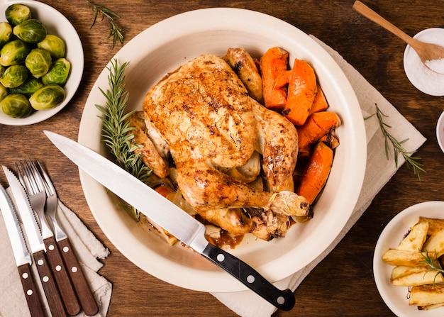 Płaski talerz z pieczonym kurczakiem w święto dziękczynienia i innymi potrawami