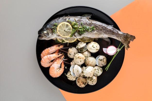 Płaski talerz z rybami i małżami