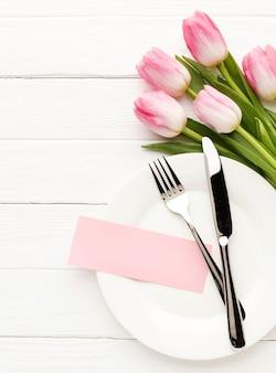 Płaski talerz z sztućcami i tulipanami obok