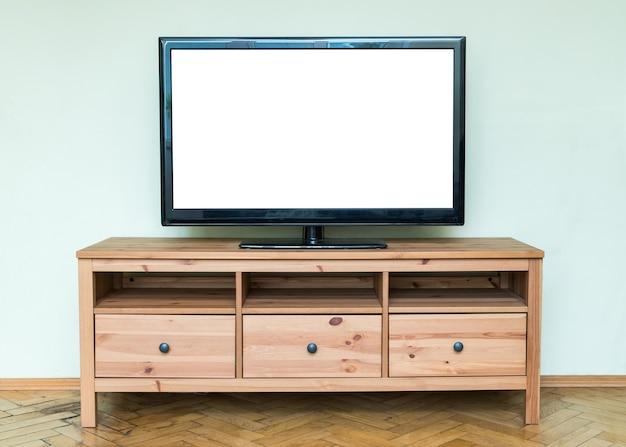 Płaski telewizor lcd na brązowej drewnianej szafce w salonie.