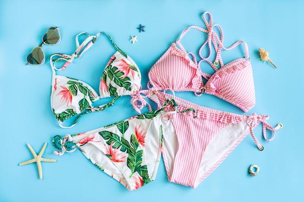 Płaski układ 2 kolorowych bikini i okularów przeciwsłonecznych w kształcie serca na niebieskim tle, widok z góry. koncepcja lato.