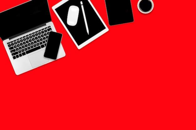 Płaski układ biurowego stołu z laptopem, cyfrowym tabletem, telefonem komórkowym i akcesoriami.