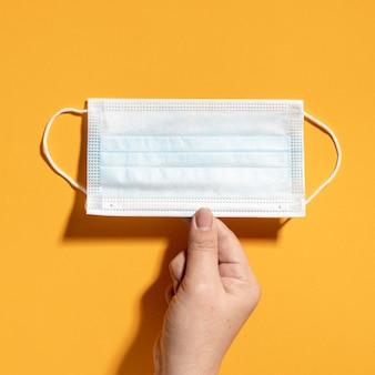 Płaski układ dłoni trzymającej maskę medyczną