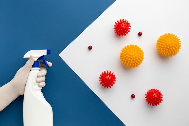 Płaski układ dłoni trzymającej środek dezynfekujący przed wirusami