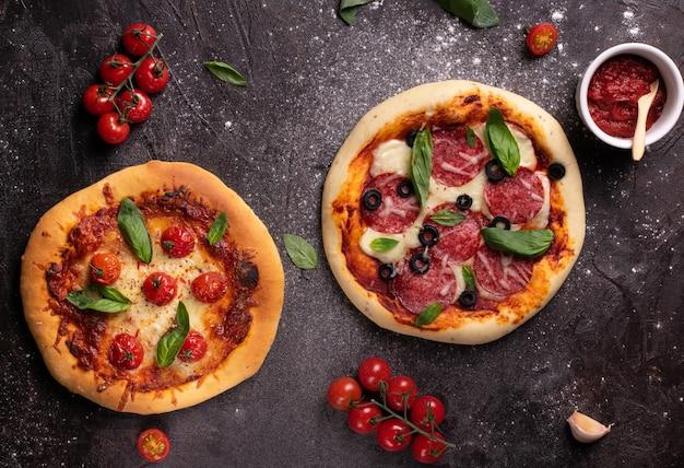 Płaski układ dwóch pizzy z pomidorami i bazylią na czarnym stole