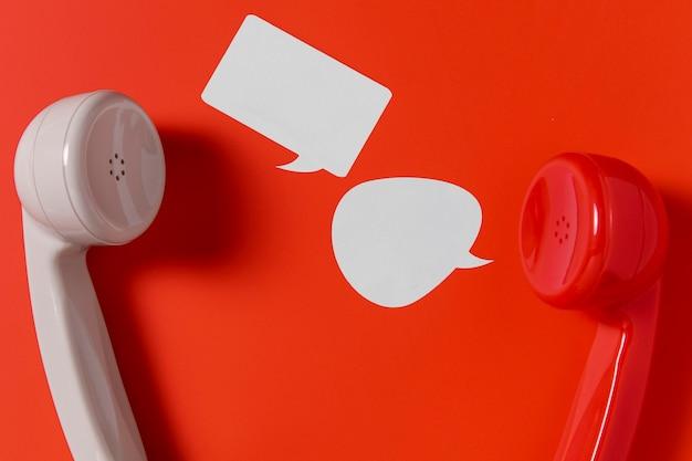 Płaski układ dymków na czacie z dwoma słuchawkami telefonicznymi