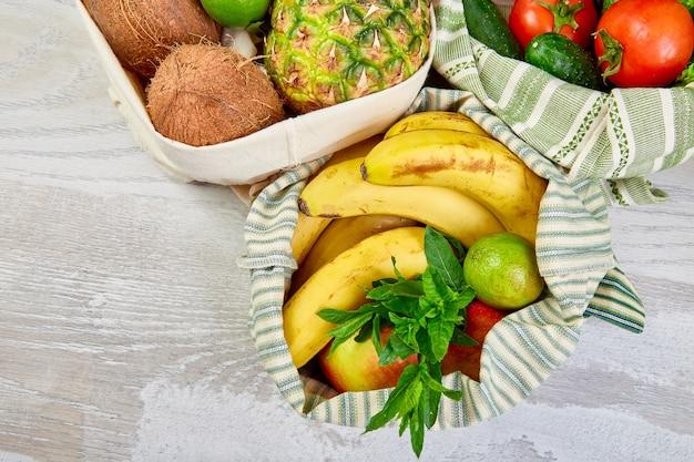 Płaski układ ekologicznych bawełnianych toreb na zakupy spożywcze z ekologicznymi owocami i warzywami