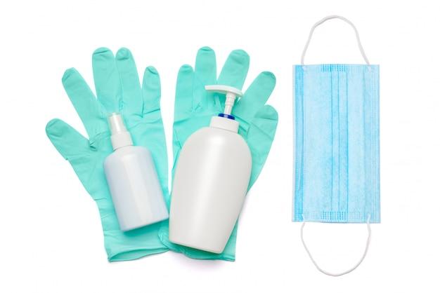 Płaski układ elementów higieny - rękawiczki lateksowe, maska i środek dezynfekujący do rąk lub mydło w płynie na białym tle na białej ścianie z przycinaniem parh.