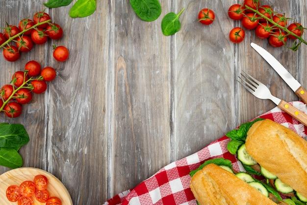 Płaski układ kanapek z pomidorami i sztućcami