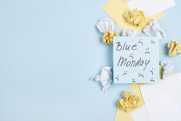 Płaski układ karteczek samoprzylepnych z marszczonymi brwiami na niebieski poniedziałek