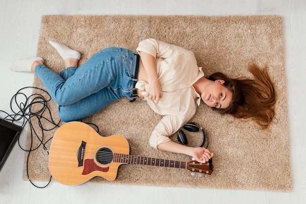 Płaski układ kobieta muzyk na podłodze w domu ze słuchawkami i gitarą akustyczną