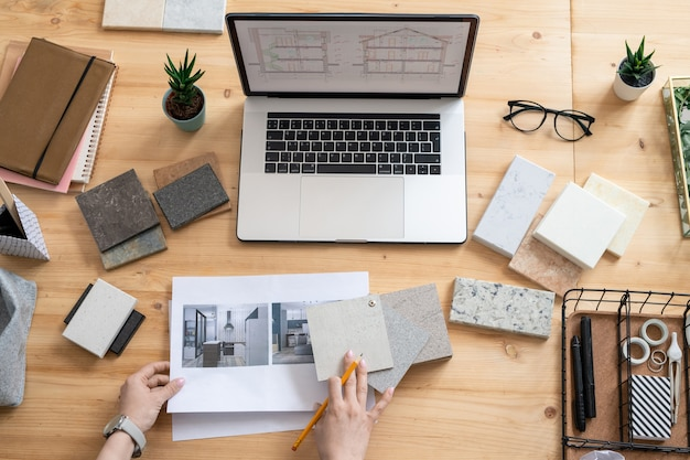 Płaski układ ludzkich rąk ołówkiem na próbkach paneli i papierach ze zdjęciami pomieszczeń w nowoczesnych domach podczas pracy