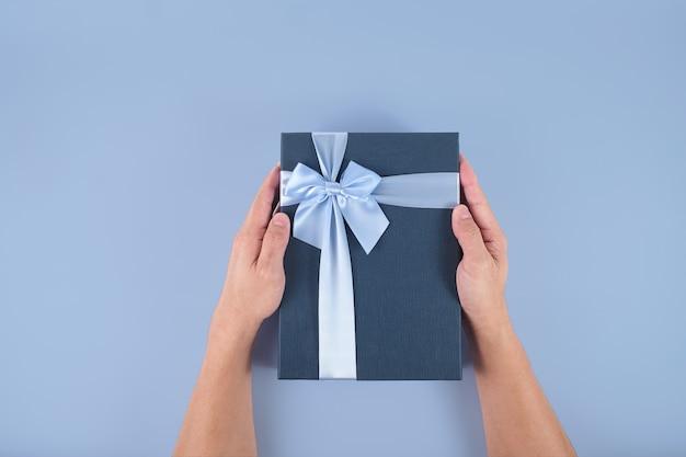 Płaski układ męskiej ręki trzymającej ozdobne ciemnoniebieskie pudełko z jasnoniebieską kokardą na pastelowym tle, ręka mężczyzny i zapakowane pudełko ze ścieżką przycinającą