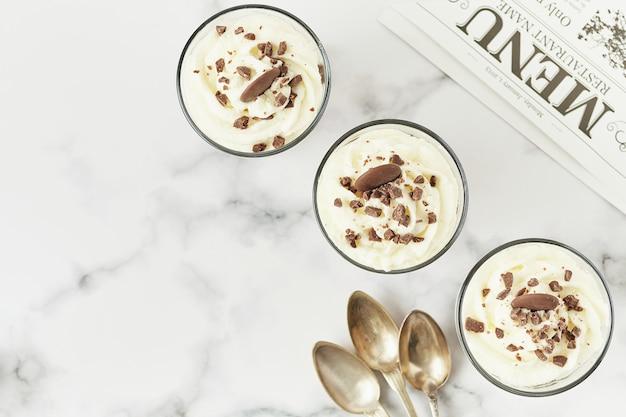 Płaski układ musu czekoladowego i kremowej filiżanki do menu restauracji z łyżeczkami