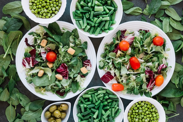 Płaski układ naczyń z sałatkami i zieloną fasolą