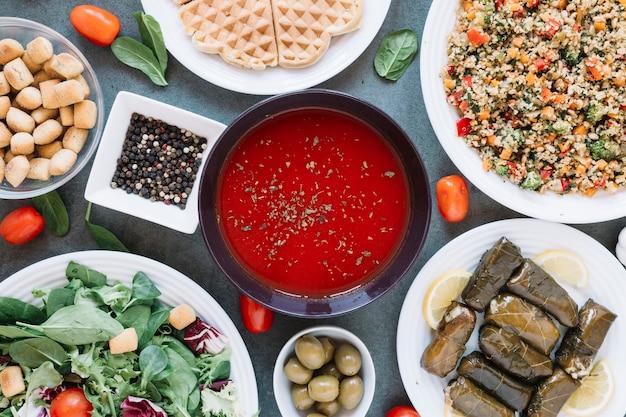Płaski układ naczyń z zupą pomidorową i pieprzem
