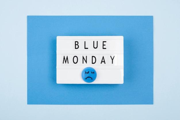 Płaski układ niebieskiego poniedziałkowego podświetlanego pudełka ze smutną twarzą