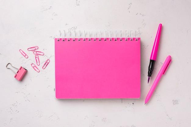 Płaski układ notebooka na biurku z długopisem i spinaczami do papieru
