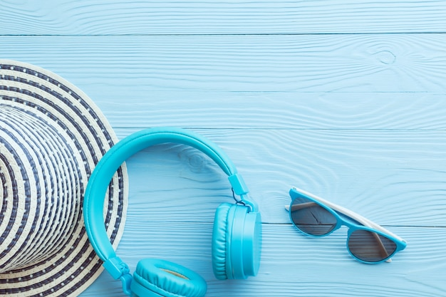 Płaski układ nowoczesnych, dużych słuchawek, czapki i okularów przeciwsłonecznych w niebieskich kolorach, ułożonych na niebieskim drewnie.