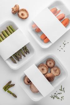 Płaski układ plastikowych opakowań z grzybami, szparagami i marchewką