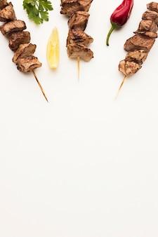 Płaski układ pysznego kebaba z cytryną i papryczką chili