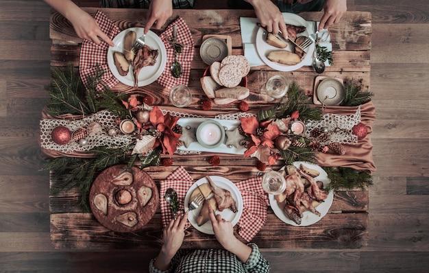 Płaski układ rąk przyjaciół, jedzących i pijących razem. widok z góry osób posiadających imprezę, spotkania, świętuje razem przy drewnianym stole rustykalnym