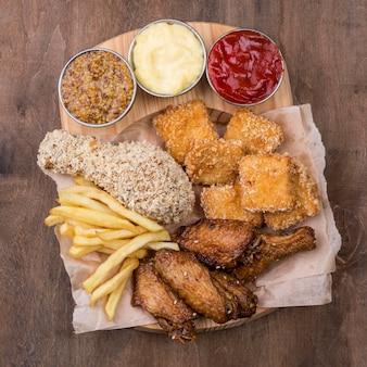 Płaski układ różnych rodzajów sosów i smażonego kurczaka