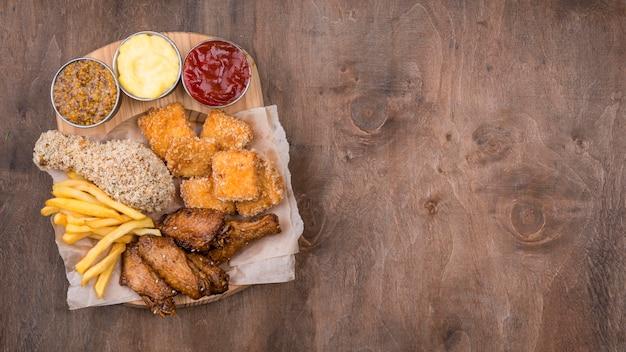 Płaski układ smażonego kurczaka z różnymi rodzajami sosu i miejsca na kopię