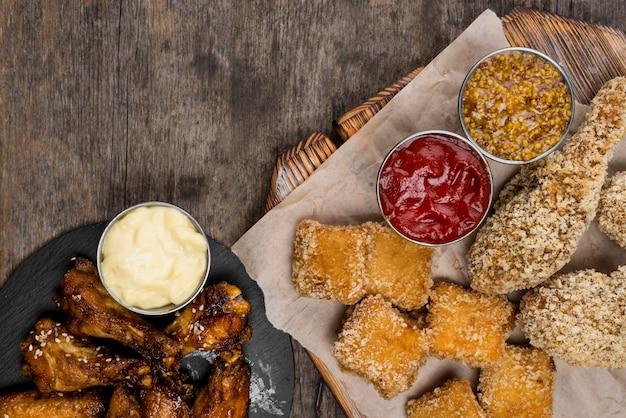 Płaski układ smażonych bryłek kurczaka z trzema sosami