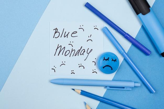 Płaski układ smutnej twarzy z ołówkami i markerem na niebieski poniedziałek