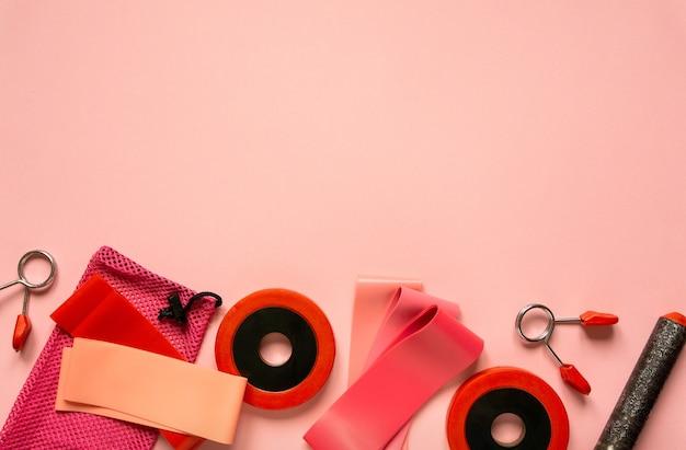 Płaski układ sprzętu sportowego. gumki fitness i hantle na różowym tle, miejsca na tekst.