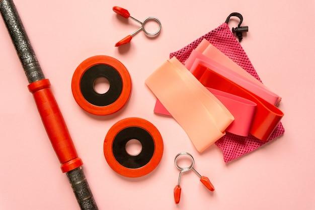 Płaski układ sprzętu sportowego. gumki fitness i hantle na różowym tle.