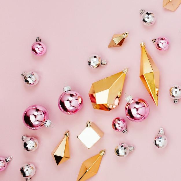 Płaski układ świąteczny świeckich ze stylowymi świątecznymi błyszczącymi kulkami i złotymi kryształami na pastelowym różowym tle. płaski układanie, widok z góry