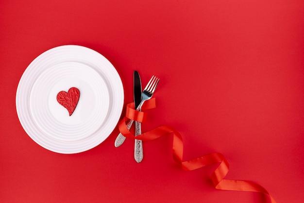 Płaski układ sztućców z sercem na talerzu i miejsce