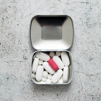 Płaski układ tabletek w metalowym pojemniku na betonowej powierzchni