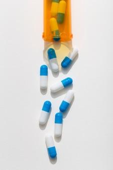 Płaski układ tabletek wychodzących z plastikowego pojemnika