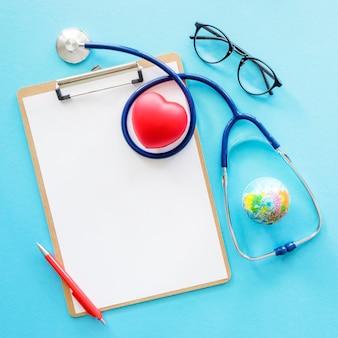 Płaski układ w kształcie serca ze stetoskopem i notatnikiem