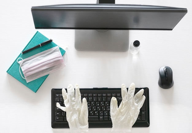 Płaski układ, widok z góry praca z domu i koncepcja zapobiegania covid-19 na drewnianym biurku biurowym, laptop z czystym żelem i maską, rękawiczki medyczne i materiały eksploatacyjne z miejscem na kopię