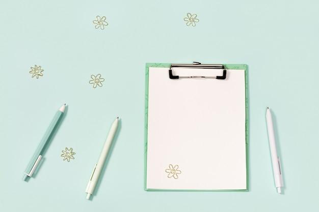 Płaski układ z artykułami biurowymi, papierowym tabletem z klipsem, długopisami, linijką i metalowymi spinaczami do papieru